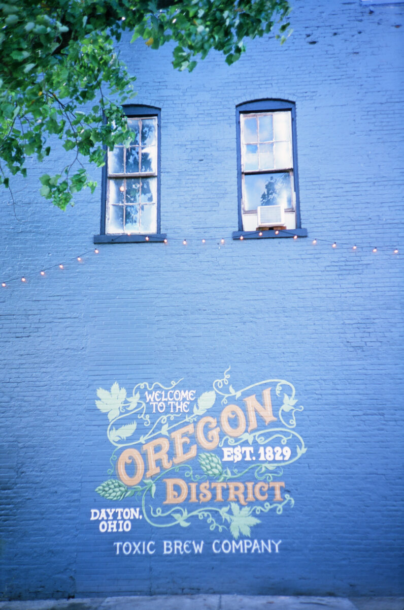 """Painted on a bright blue wall beneath two blue-framed windows are the words, """"Welcome to the Oregon District."""""""